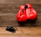 两个红色拳击手套在木棕色背景,跳绳垂悬了 免版税库存照片