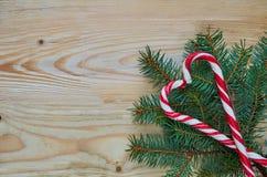 两个红色糖果锥体的心脏在圣诞树的分支与在左边的赠送阅本空间 新年或情人节甜点 库存照片