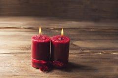 两个红色蜡烛栓与红色丝带,华伦泰` s天的标志,仿造物人关系和妇女 免版税库存图片