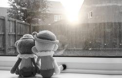 两个编织的玩偶握手坐在窗口旁边,黑白颜色的男孩和女孩 免版税库存图片