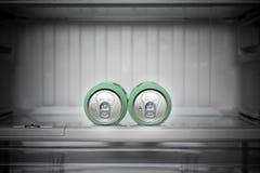 两个罐头啤酒在一个空的冰箱在 库存照片