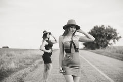 两个美丽的典雅的女孩黑白色摄影帽子的,户外晴朗的夏日背景 免版税库存图片