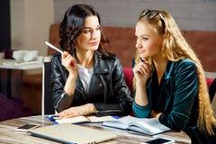 两个美丽的女学生为在咖啡馆的研讨会准备着 免版税库存照片