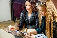 两个美丽的女学生为在咖啡馆的研讨会准备着 免版税库存图片