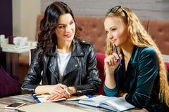 两个美丽的女学生为在咖啡馆的研讨会准备着 库存图片