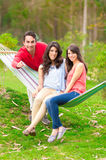 两个美丽的女孩和一个年轻人吊床的 免版税库存图片