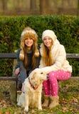 两个美丽的女孩和一条狗在公园 图库摄影