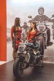 两个美丽的女孩和一辆新的高速摩托车 免版税图库摄影