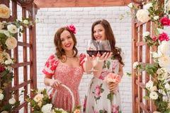 两个美丽的女孩在摆在与杯的花曲拱下的夏天礼服在手上穿戴了红葡萄酒 库存照片