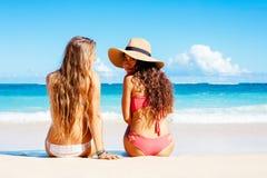 两个美丽的女孩坐海滩 库存照片