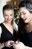 两个美丽的女孩微笑的使用与电话在度假 免版税库存图片