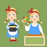 两个美丽的女孩烹调可口盘 免版税库存照片