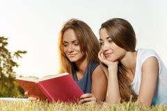 两个美丽的女孩阅读书在公园 免版税库存照片