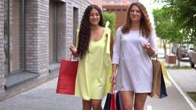 两个美丽的女朋友在购物以后运载不同的颜色包裹与购物的 慢的行动 影视素材