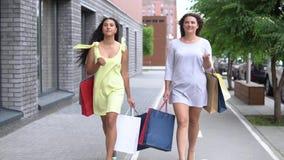 两个美丽的女朋友在购物以后运载不同的颜色包裹与购物的 慢的行动 HD 股票录像