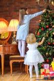 两个美丽的姐妹装饰圣诞树 图库摄影