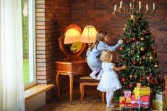 两个美丽的姐妹装饰圣诞树 免版税库存图片