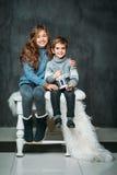 两个美丽的孩子画象在毛线衣和牛仔裤穿戴了在葡萄酒背景 库存图片