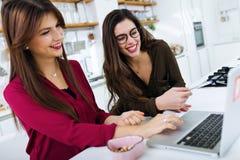两个美丽的少妇与膝上型计算机一起使用在厨房里 库存照片