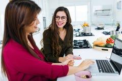 两个美丽的少妇与膝上型计算机一起使用在厨房里 免版税库存照片