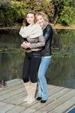 两个美丽的少妇和池塘在秋天停放 库存图片