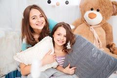 两个美丽的微笑的姐妹画象有枕头的 免版税库存照片