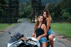 两个美丽的性感的女孩坐黑白摩托车的颜色 在黑球衣和牛仔布穿戴的模型 免版税库存照片