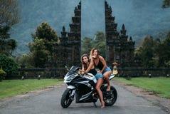 两个美丽的性感的女孩坐黑白摩托车的颜色 在黑球衣和牛仔布穿戴的模型 库存照片