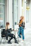 两个美丽的年轻白肤金发的女孩喝咖啡和谈话在咖啡馆附近 免版税图库摄影
