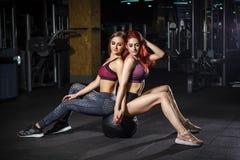 两个美好的健身运动的女孩坐在健身房的体操球 库存照片
