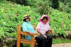 两个老妇人坐一把椅子在庭院里 免版税库存图片