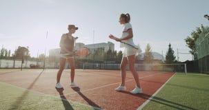 两个职业玩家夫人有一次小的交谈在网球赌博,打的手和完成的前 股票视频