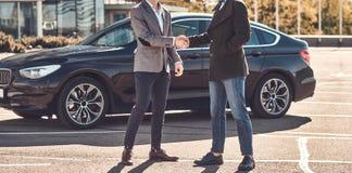 两个聪明的典雅的人照片,有关于汽车的一个成交 免版税库存图片