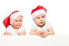 两个胖的婴孩戴红色圣诞节帽子 免版税库存图片
