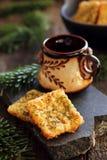 两个自创乳酪薄脆饼干和一个杯子在石头 库存照片