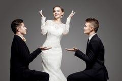 两个英俊的人和美丽的新娘,演播室 免版税库存图片