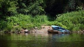 两个荡桨的渔船在Neman R的绿色夏天海滩停泊了 库存照片