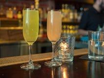 两个葡萄酒杯充满含羞草喝坐酒吧计数 免版税库存图片
