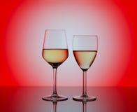 两个葡萄酒杯用在红色背景的白葡萄酒 免版税库存图片