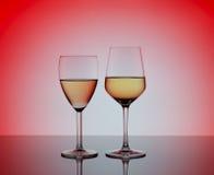 两个葡萄酒杯用在被弄脏的红色背景的白葡萄酒 库存照片