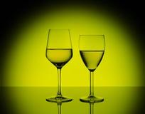 两个葡萄酒杯用在被弄脏的黄色背景的白葡萄酒 免版税库存照片