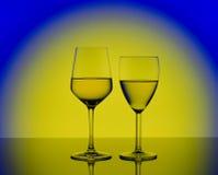 两个葡萄酒杯用在被弄脏的黄色背景的白葡萄酒 库存图片