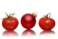两个蕃茄和一个红色圣诞节球 图库摄影