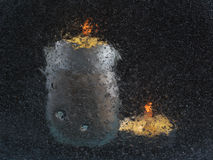 两个蜡烛,射击通过与气泡的一块玻璃:蜡烛隐晦的剪影在黑背景的 库存照片