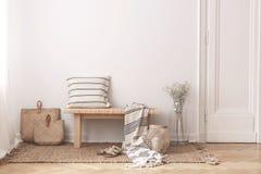 两个袋子由秸杆制成在与镶边枕头的木桌旁边 免版税库存照片