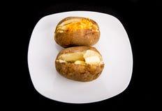两个被烘烤的土豆用黄油和乳酪 免版税库存照片