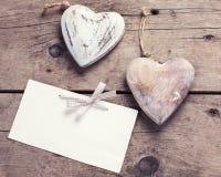 两个装饰心脏和空标识符在年迈的木背景 免版税库存图片