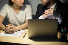 两个谈论的企业同事特写镜头在夜办公室 库存照片
