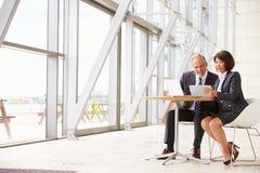 两个资深企业同事在会议上在现代内部 免版税库存照片