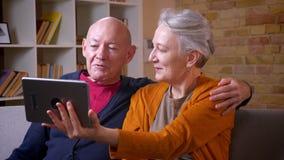 两个资深灰发的白种人配偶谈话在体贴爱抚的片剂的videochat在舒适家 影视素材